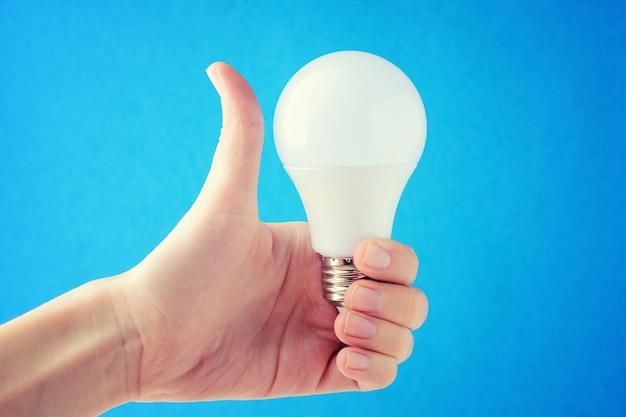 A mulher está segurando uma lâmpada nas mãos e mostrando o l