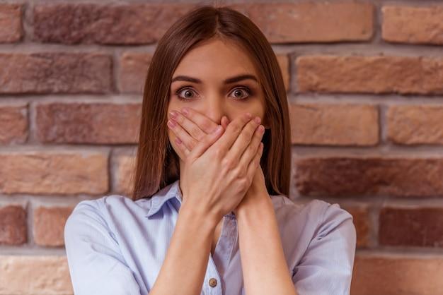 A mulher está sorrindo olhando in camera e mostrando surpresa.