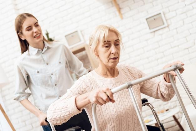 A mulher está tentando levantar-se da cadeira de rodas.