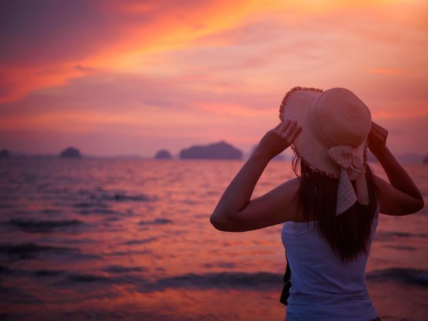 A mulher está vestindo o chapéu do verão e estando sozinho na praia durante o por do sol.