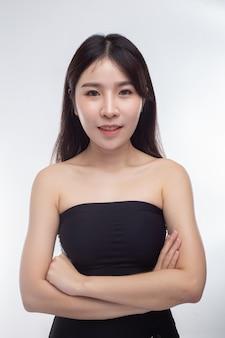 A mulher está vestindo uma camisa sem alças que fica com os braços cruzados