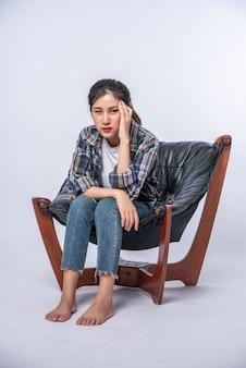 A mulher estava doente, sentou-se em uma cadeira e tocou a cabeça com a mão.