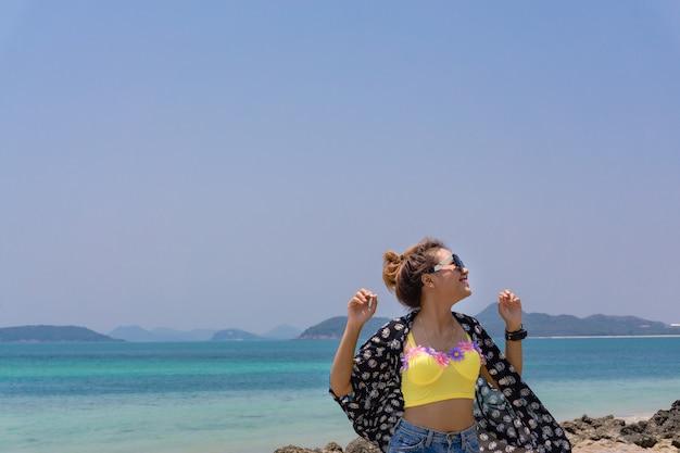 A mulher estava em pé na praia e o clima no verão.