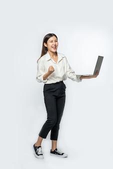 A mulher estava vestindo uma camisa branca e calça escura, segurando um laptop e fingindo estar feliz