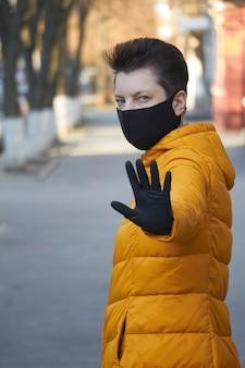 A mulher européia envelhecida média na máscara preta protetora faz um gesto de aviso durante a epidemia de coronavírus covid-19. mulher doente usando proteção durante uma pandemia.
