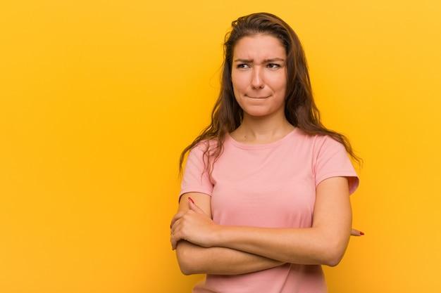 A mulher européia nova isolada sobre amarelo confuso, sente duvidoso e incerto.