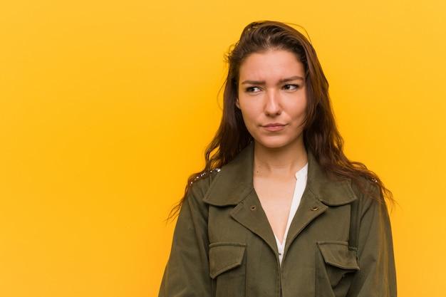 A mulher européia nova isolada sobre o amarelo confundido, sente duvidosa e insegura.