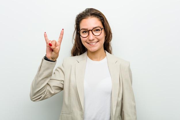 A mulher européia nova mostrando chifres gesticula como um conceito da revolução.