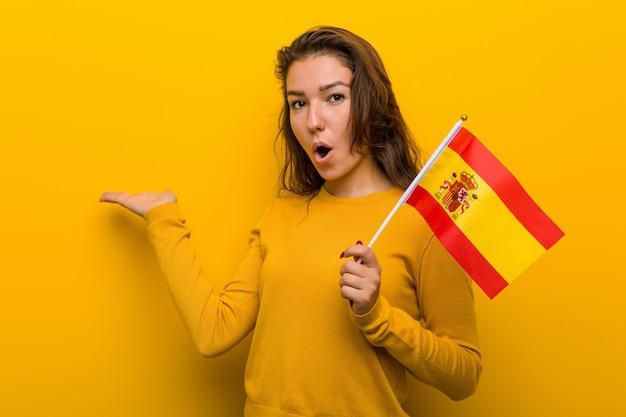 A mulher européia nova que guarda uma bandeira espanhola imprimiu guardar a palma do copyspace.