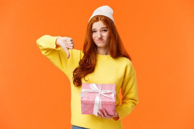 A mulher exigente ruiva bonito cética e desajeitada não gosta do presente de natal da tia, mostra o polegar para baixo