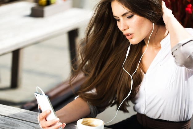 A mulher fala via fones de ouvido no telefone