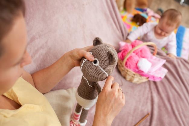 A mulher faz amigurumi de brinquedo para os olhos