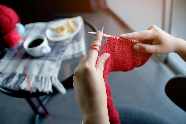 A mulher faz malha o lenço de lã do círculo, agulhas de confecção de malhas.