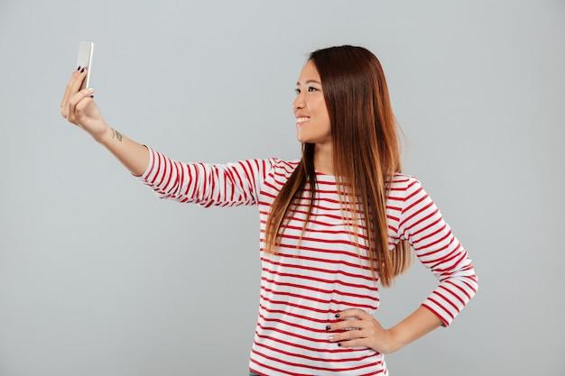 A mulher faz o selfie pelo telefone que está isolado