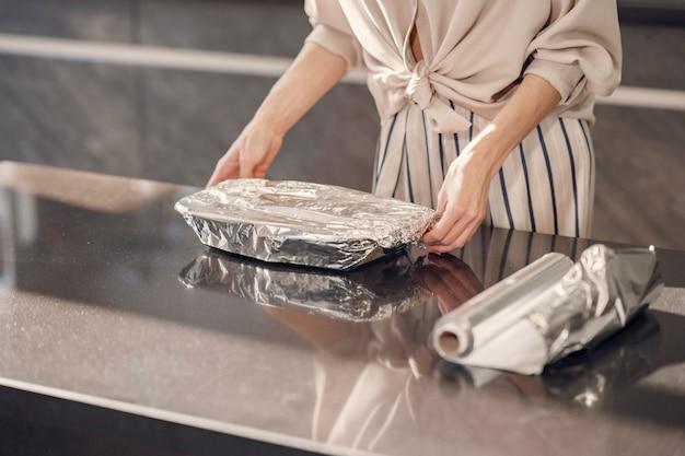 A mulher faz um jantar na cozinha em casa