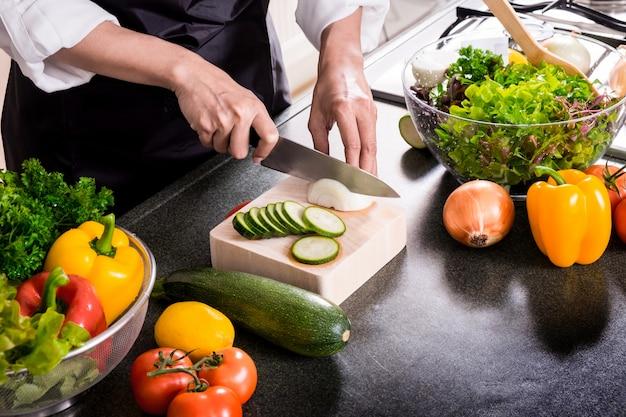 A mulher faz uma salada de vegetais frescos