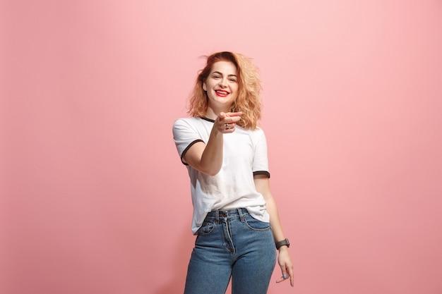 A mulher feliz aponta e quer você, retrato de closeup meio comprimento na parede rosa.