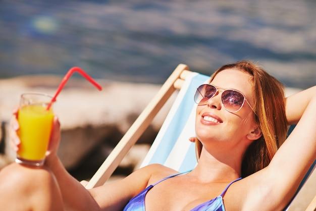 A mulher feliz beber um sumo de laranja na praia
