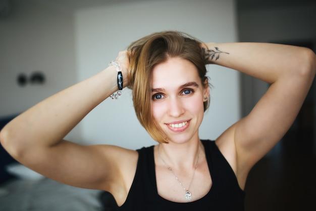 A mulher feliz bonita com tatuagem na mão endireita seu cabelo, olha na câmera e ri.