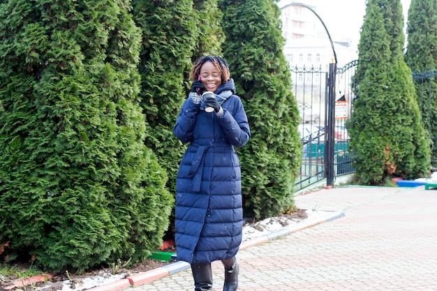 A mulher feliz caminha pela rua no inverno