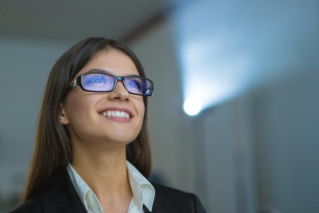A mulher feliz com óculos no fundo do projetor