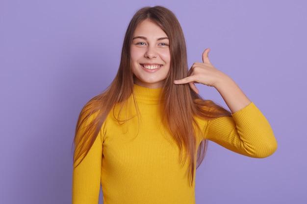 A mulher feliz de sorriso veste a exibição amarela da camisa chama-me gesto
