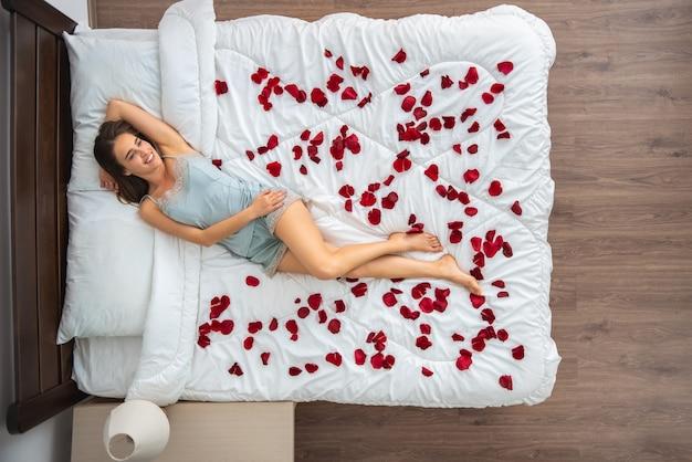 A mulher feliz deitada na cama com pétalas de rosa. vista de cima
