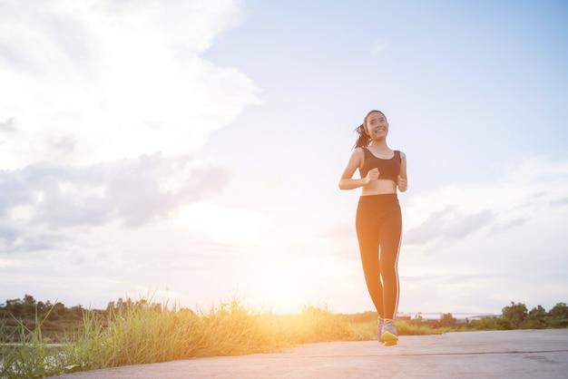 A mulher feliz do corredor corre no exercício movimentando-se do parque.