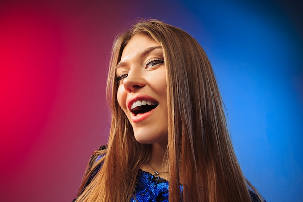 A mulher feliz em pé e sorrindo contra o espaço colorido.