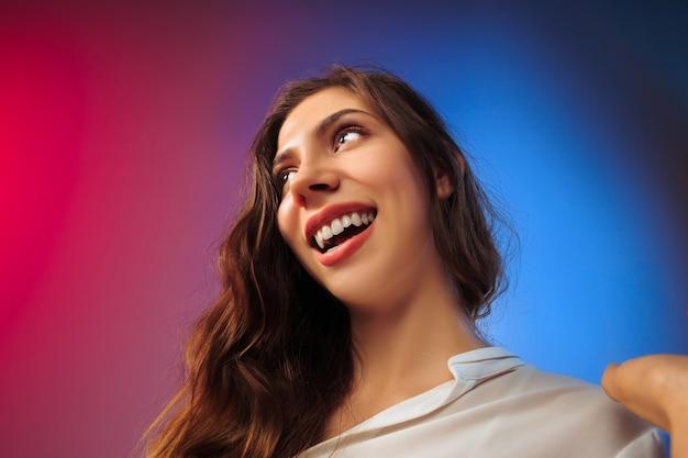 A mulher feliz em pé e sorrindo contra os coloridos.