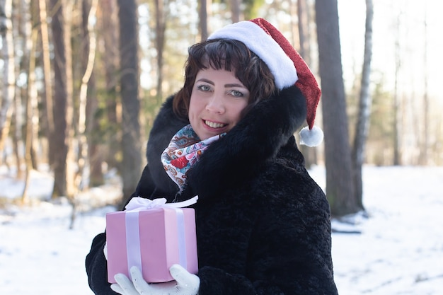 A mulher feliz em um corpo na natureza no inverno com um presente, o natal