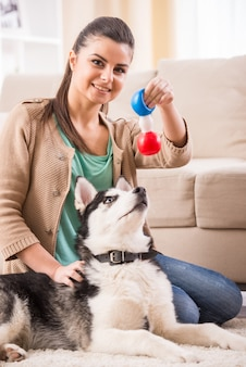 A mulher feliz está jogando com seu cão em casa.