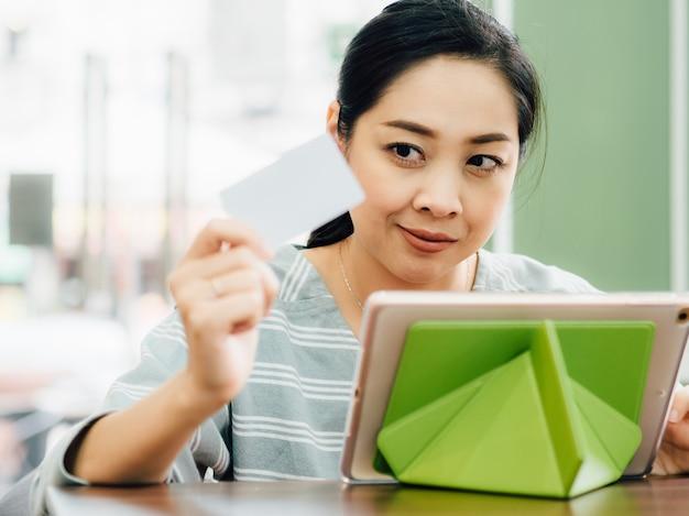 A mulher feliz está usando um cartão de crédito branco do modelo para a compra em linha na tabuleta.