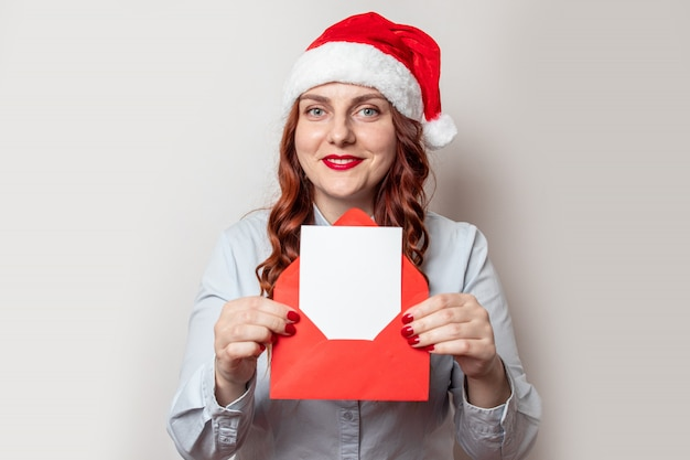 A mulher feliz no chapéu sanya pensa no natal com carta de desejo ou lista em envelope vermelho nas mãos na véspera de natal