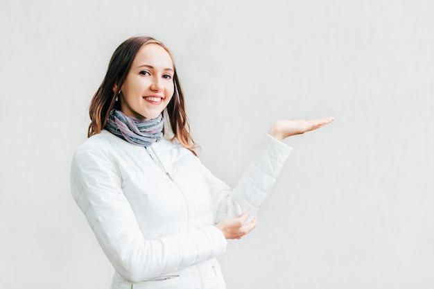 A mulher feliz que guarda sua mão para apresentar qualquer coisa e olha na lente.