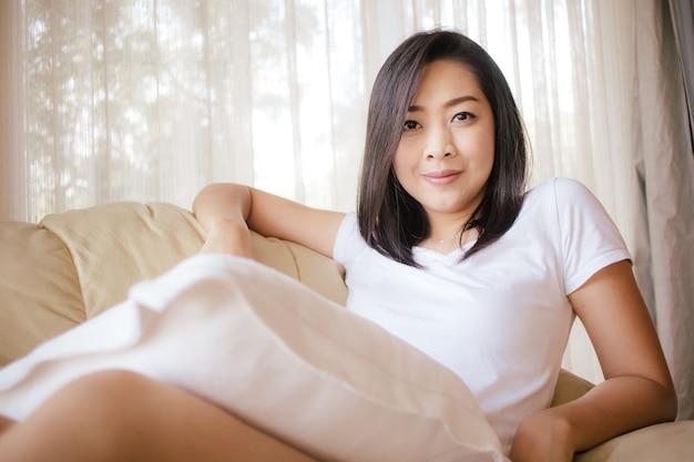 A mulher feliz relaxa com café e luz da manhã na sala de visitas.