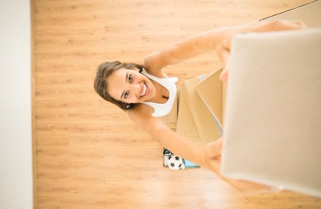 A mulher feliz segura uma caixa de papelão e olha para a câmera. vista de cima