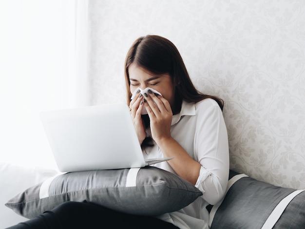 A mulher fica doente durante o trabalho com o portátil em casa.