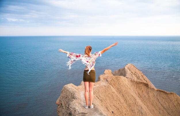 A mulher fica no mar com os braços abertos como asas