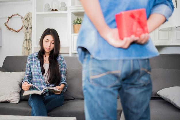 A mulher ficará surpresa com o presente de seu namorado em casa quando lê livros e não está pronto para se surpreender