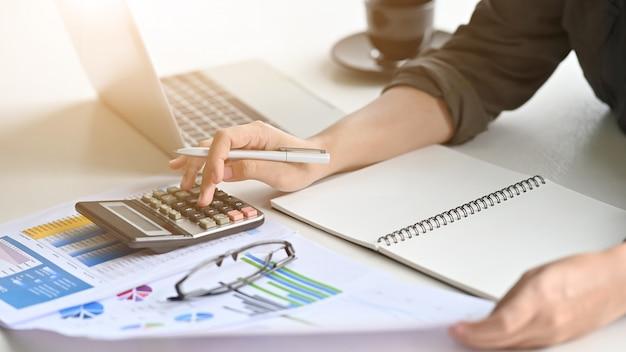 A mulher financeira da motivação do close up calcula dados na mesa de escritório.