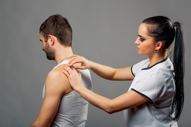 A mulher fisioterapeuta no vestido branco que examina equipa para trás isolado na cinza