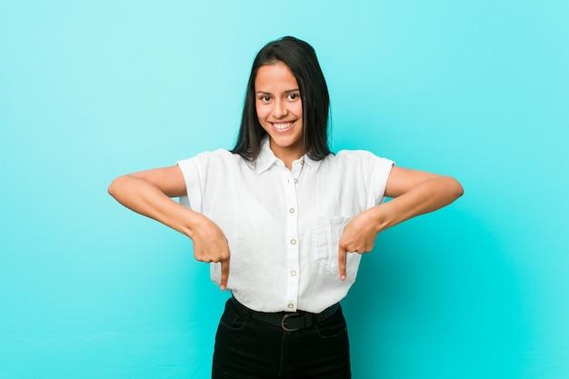 A mulher fresca latino-americano nova contra uma parede azul aponta para baixo com dedos, sentimento positivo.