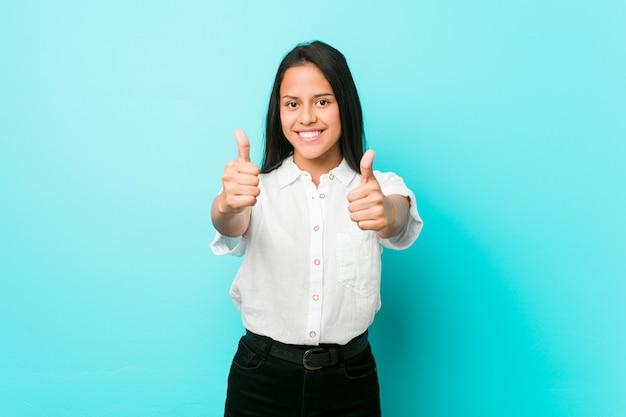 A mulher fresca latino-americano nova contra uma parede azul com polegares levanta, elogios sobre algo, apoia e respeita o conceito.