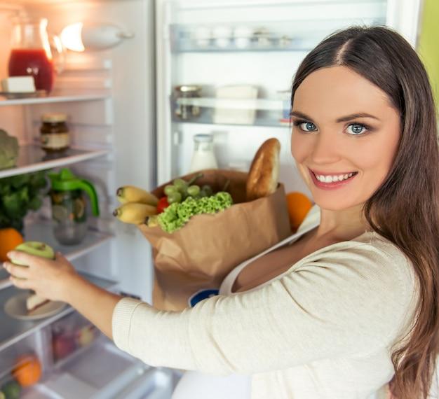 A mulher gravida bonita está guardando um saco de papel com alimento.
