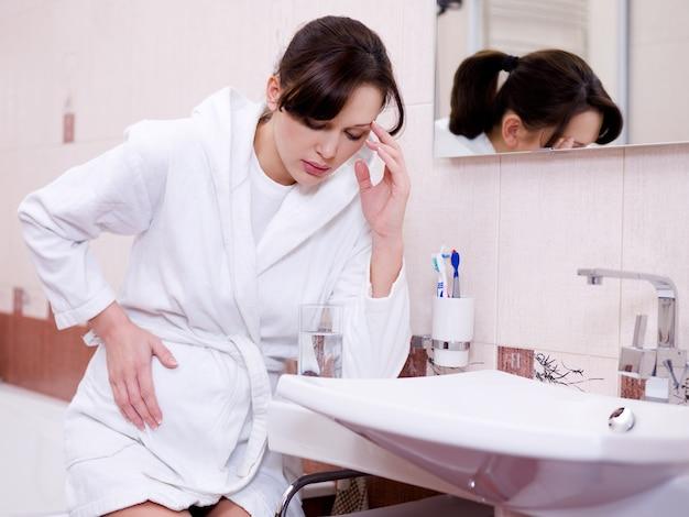 A mulher grávida com uma forte intoxicação sentada no banheiro