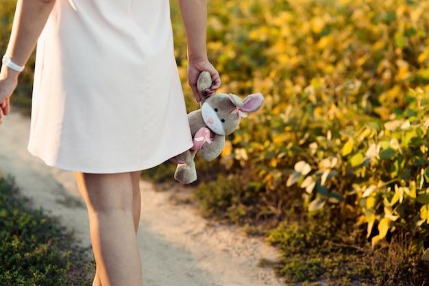 A mulher grávida com vestido rosa segura coelho cinza em seu braço macio