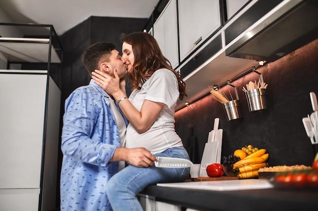 A mulher gravida e o homem bonitos de sorriso na cozinha bebem o café e cozinham. à espera de uma nova vida, gravidez.