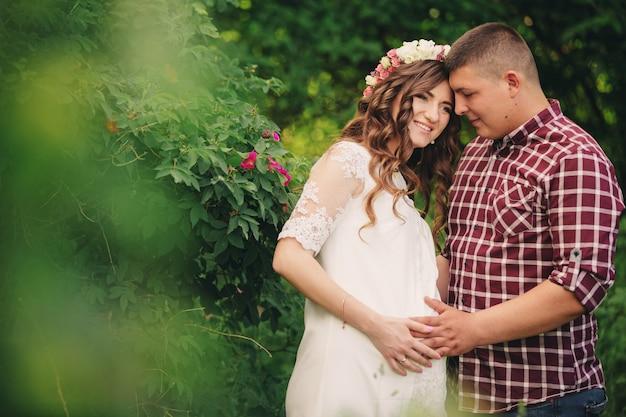 A mulher grávida e o marido estão felizes em abraçar, dar as mãos no estômago, ficar ao ar livre no fundo verde do jardim. fechar-se.