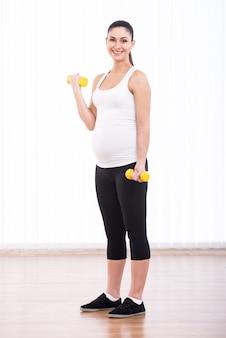 A mulher gravida está fazendo o esporte com dumbbells.